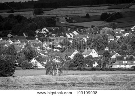 View of the small town of Neustadt (Marburg-Biedenkopf district in Hessen) the suburbs and surrounding agricultural land in the morning sun. Black and white.