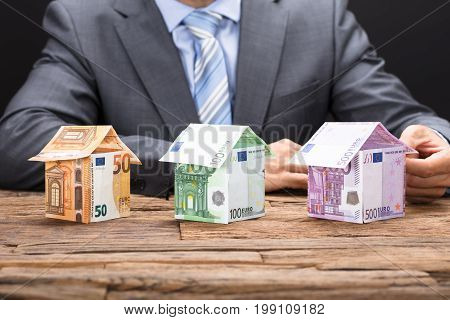 Businessman making houses from euro paper currencies on wooden table against black background