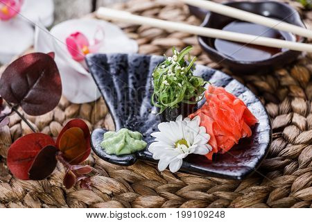 Sushi Gunkan maki with seaweed sesame and cream cheese on black plate on bamboo mat decorated with flowers. Japanese cuisine. Selective focus