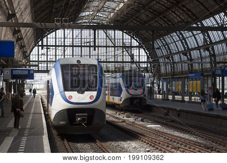 AMSTERDAM, THE NETHERLANDS - MAY 24, 2017:Two sprinter trains of dutch railway, in Amsterdam's historic central train station. And waiting travelers