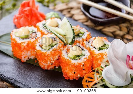 Sushi Roll - Maki Sushi made of Salmon Red caviar cucumber avocado and cream cheese on black stone on bamboo mat decorated with flowers. Japanese cuisine