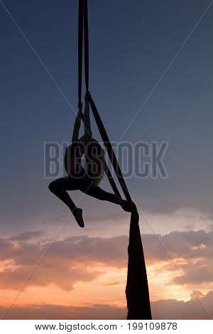 woman's silhouette in air against the background of the evening zakazt she carries out acrobatic tricks on cloths.