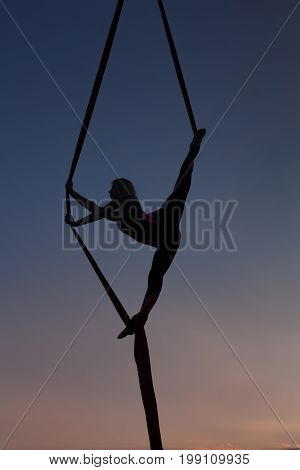 Female silhouette during acrobatic numbers against the background of the evening sky.