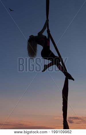 Woman acrobat dances on on canvases. Silhouette against the background of the evening sky.