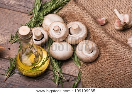 A view from above of a picture of big natural white mushrooms and garlic on a brown wooden background. A transparent capacity full of sunflowers yellow oil and fresh rosemary on a rustic fabric.