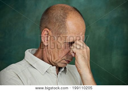 Worried mature man touching his head and thinking on studio background.