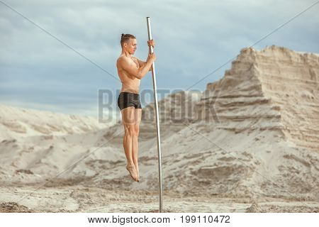 Guy is doing gymnastics on the pole in the desert among the sand.