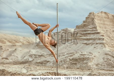 Male gymnast does tricks on a pylon in the desert on the sand.