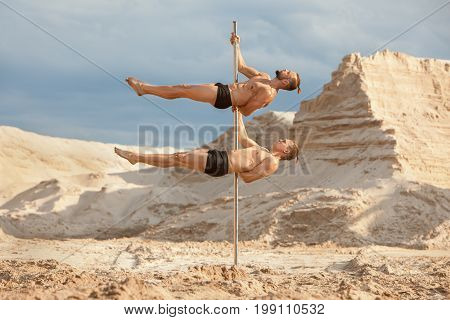 Two men of acrobats dance on a pylon in the background a desert and sand.