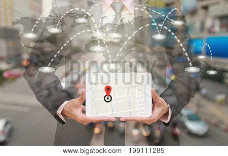 Businessman holding a tablet showing part of navigator map on connection line over the world map with blurred photo of traffic jam Navigation conceptElements of this image furnished by NASA, 3D illustration