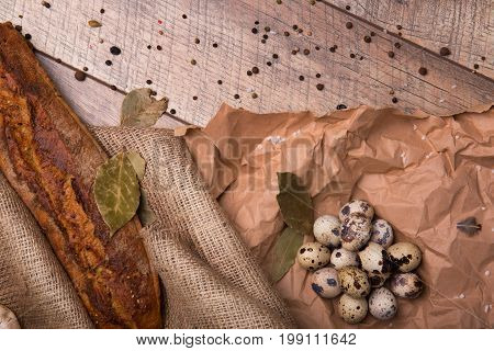 Top view of brown rye bread, speckled fresh quail eggs, dried bay leaves, grocery paper and different seasonings on a wooden background.