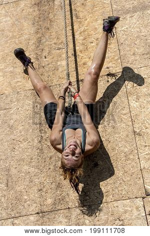 Young woman having fun and smiling; hang upside down on wooden wall with rope; concept of leisure relax playfulness and fun
