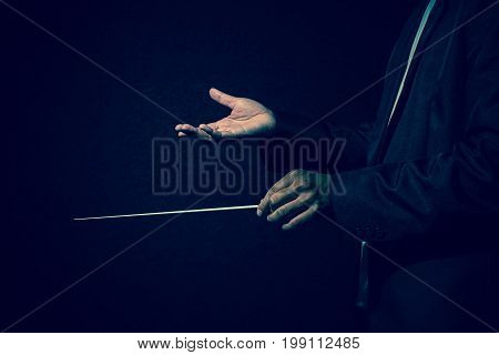 Orchestra conductor hands Musician director holding stick on dark background