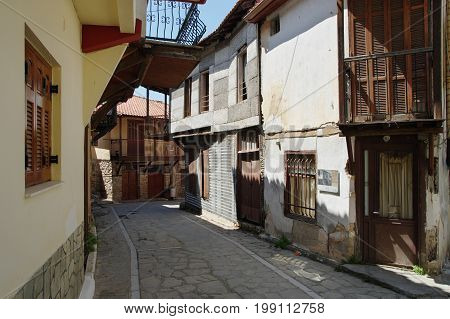 Arnea, small town near the Chalkidiki peninsula in northen Greece. Region of Macedonia. Street in the city center. Along the road are houses with typical architecture of the region.