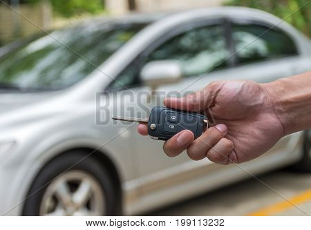 Hand holding the keys over photo blurred of used car for open the door car transportation and ownership concept
