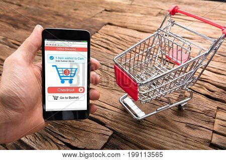 Cropped image of businessman's hand holding smartphone by shopping cart on wooden table