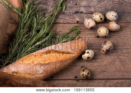 Closeup of white wheat baguette, wholesome quail eggs twigs, odorous rosemary, seasonings, a piece of a grocery paper, little eggs for good health on a light wooden background.