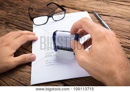 Cropped hands of businessman stamping contract paper at wooden table