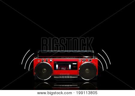 Red boom box on black background . .