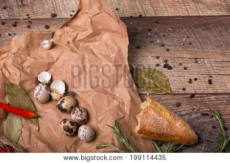 Closeup of a piece of a baguette, quail eggs with speckles, hot red chili pepper, grocery paper on a light wooden background.
