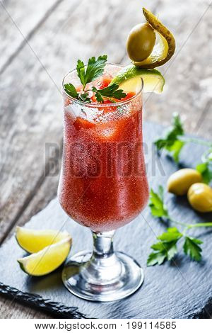 Bloody Mary cocktails with tomato juice and spicy vodka decorated with pickle and olive garnish on stone slate background on rustic table. Summer drinks and alcoholic cocktails.