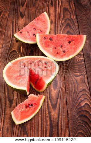 A cut watermelon on a light brown wooden background. A composition of beautiful watermelon pieces.Top view of a ripe big watermelon berry on a table. Preparation of vegan milkshakes.