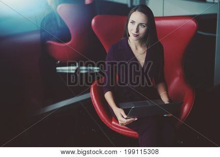 Portrait of adult pensive female entrepreneur wistfully looking aside while sitting in front of mirror on red bent armchair and holding laptop with copy space zone for text your logo or advertising
