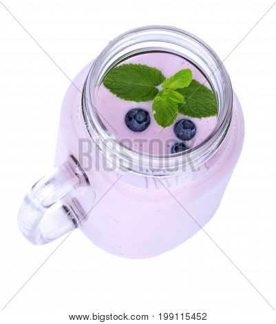 A view from above of a mason jar full of light purple blueberry smoothie with little berries and fresh mint isolated on a white background. Nutritious cocktails for healthy breakfasts.
