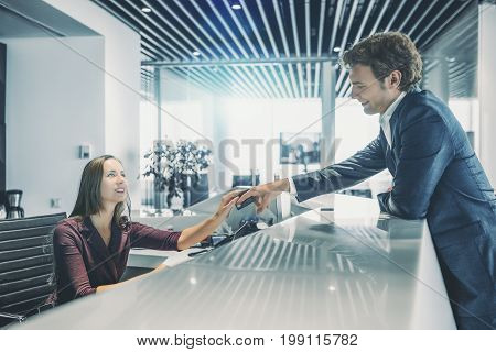 Smiling handsome man in formal suit is leaning on table top and giving his debit card to charming caucasian woman working on reception to pay his bills modern bright interior of office or hotel