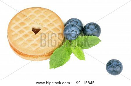 A view from above on a perfect light brown cookie with a heart. Juicy blueberries, mint leaves and a crunchy biscuit isolated on a white background. Baked and homemade organic snacks.