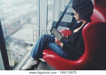Side view of biracial pensive business girl with afro hair sitting on red bent armchair in front of office panoramic windows and preparing to future work meeting using her digital tablet