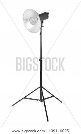 Professional photo studio flashlight isolated over the white background. Photographic light on a long tripod. A reflector and outbreak on a tripod. Dark black photo equipment.