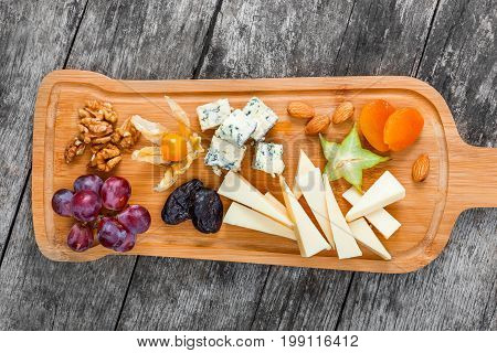 Cheese platter garnished with pear honey walnuts grapes carambola physalis on cutting board on wooden background. Snacks and Wine appetizers set. Top view