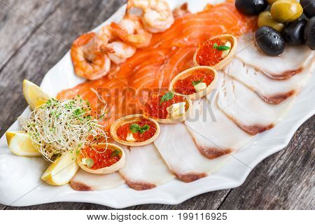 Seafood platter with salmon slice pangasius fish red caviar shrimp decorated with olives and lemon on wooden background close up. Mediterranean appetizers. Top view