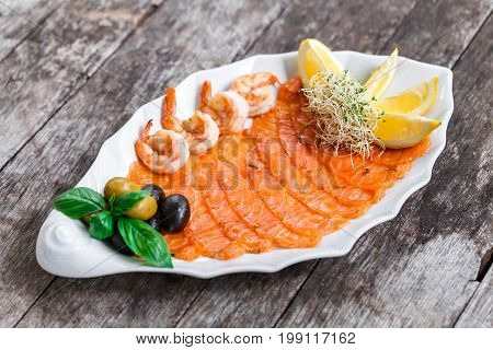 Seafood platter with salmon slice and shrimp decorated with olives and lemon on wooden background close up. Mediterranean appetizers. Top view