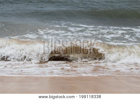 Waves lapping against the sandy shore on Maui