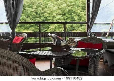 two 2 brown wicker chair with red cushion next to a table covered with glass on the porch on the table are sugar salt glass glass tubes the interior