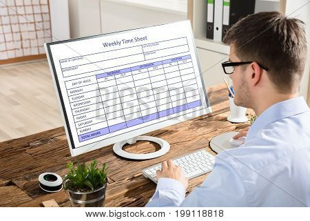 Close-up Of A Young Businessman Looking At Weekly Time Sheet On Computer In Office