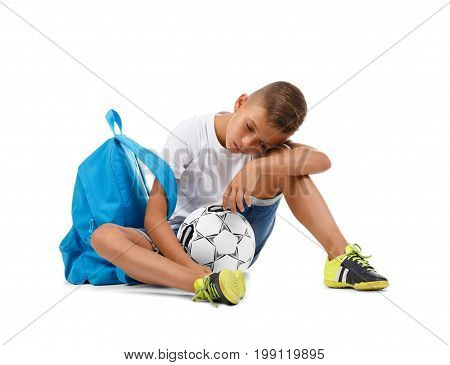 A tired boy sitting on the ground. A little soccer player isolated on a white background. Outdoors activities. Sports concept. A sportive kid with a soccer ball. Copy space.