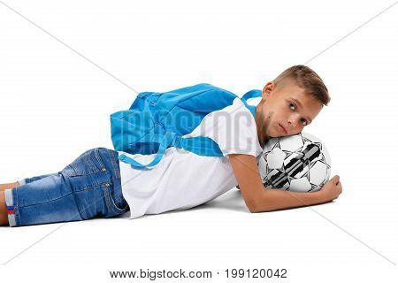 A little boy with a head on a ball. A cute tired soccer player lying on the ground. A sportive schooler with bright blue rucksack isolated on a white background. Sports concept.