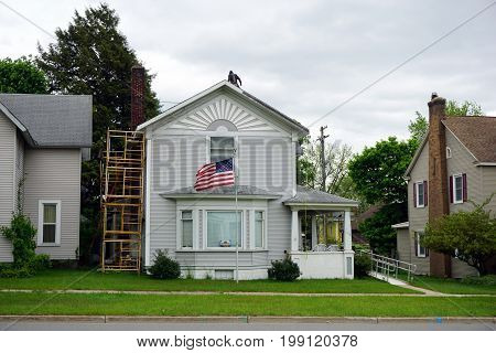 CADILLAC, MICHIGAN / UNITED STATES - MAY 31, 2017: A home, in Cadillac's Courthouse Hill Historic District, flies the American flag, while undergoing restoration.