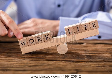 Close-up Of A Person's Finger Showing Misbalance Between Work And Life