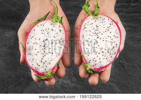 A close-up picture of cut juicy dragon fruit in male hands. Colorful ripe exotic fruit on a dark gray stone background. Perfect ingredient for summer snacks, desserts and breakfasts. Tropical pitaya fruits.