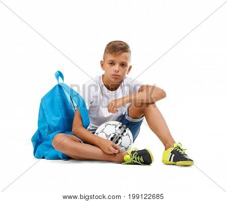 Terribly upset schooler with a soccer ball. Troubled little kid isolated on a white background. A frown boy with a ball and a blue satchel sitting on the ground. Competition game concept.