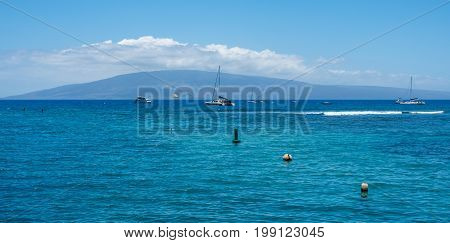 A view of boats anchored in Lahaina harbor on Maui Hawaii.