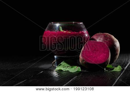 A big, fancy glass filled with saturated red beetroot juice on a black wooden background. Ripe and peeled beets for a healthful summer salad. Raw vegetable cocktails. Copy space.