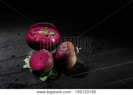 A spacious glass full of dark purple beetroot cocktail on a black table background. Nutritious beets for a healthful vegetarian salad. Vegetable juices for gourmets. Copy space.