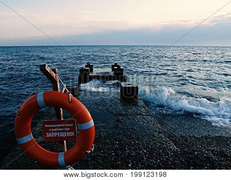 Life ring and life jacket on a pier on the background of the sea