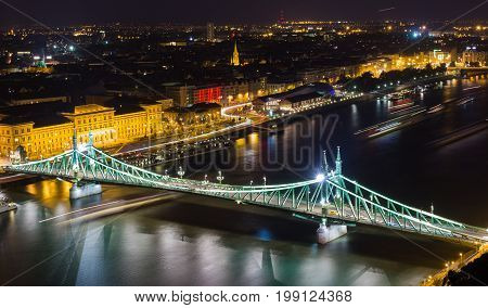 Liberty Bridge in Budapest with blurry boats passing from elevated view at night