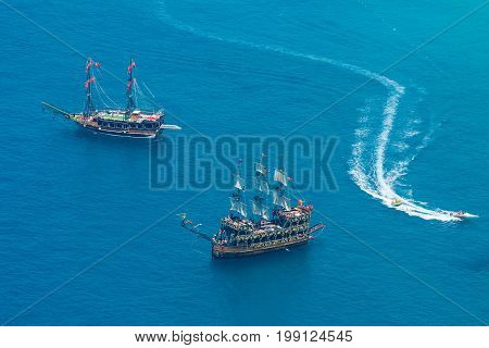 ALANYA TURKEY - JULY 09 2015: Mediterranean Sea. Traditional entertainment resort of Alanya. Sailing aka pirate ships around the fortress of Alanya. View from the bird's-eye view.